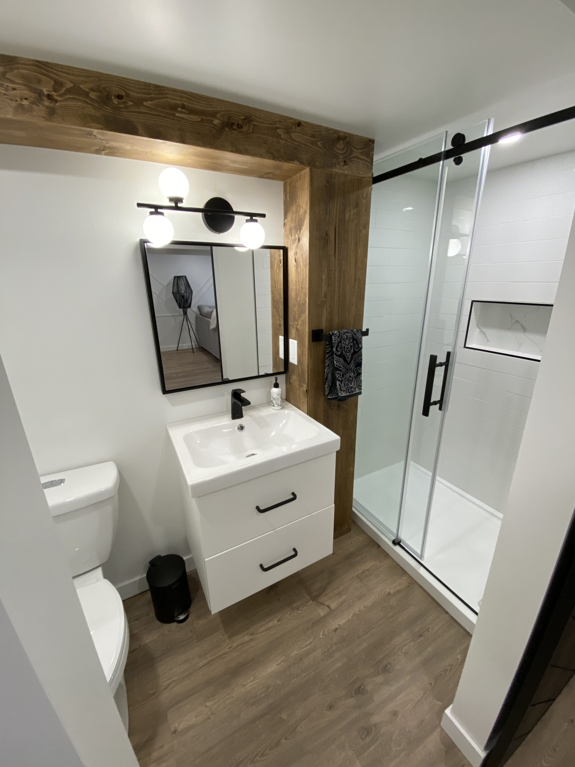 white and black basement bathroom with wood accent covering plumbing conduit