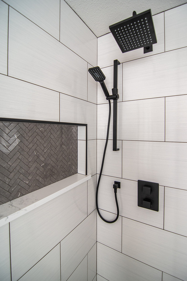 accent tile grey herringbone shower niche with black accents and dark grout