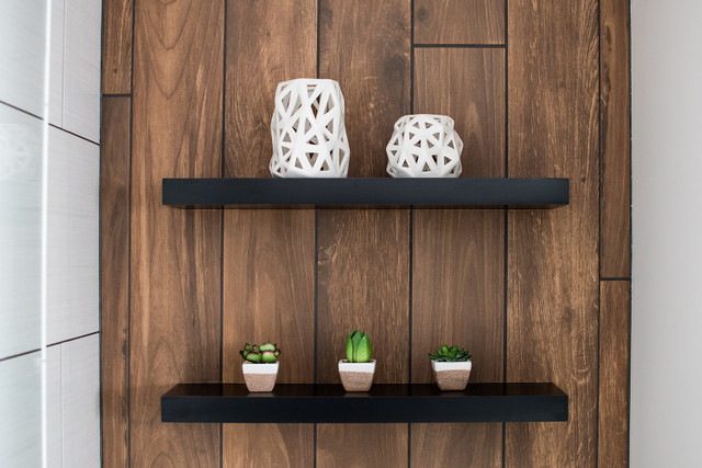 two black floating shelves in bathroom on wood accent wall