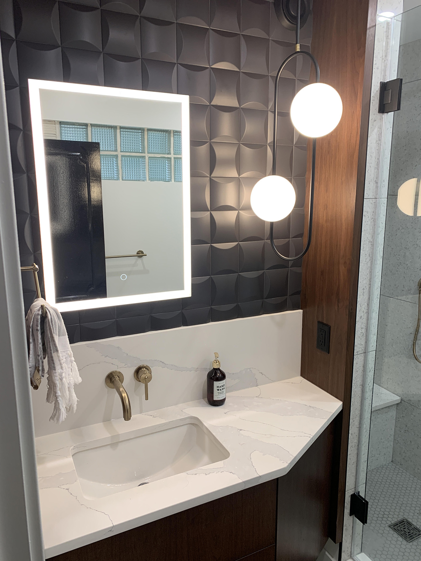 masculine bathroom renovation with modern fixtures and black square 3d tile